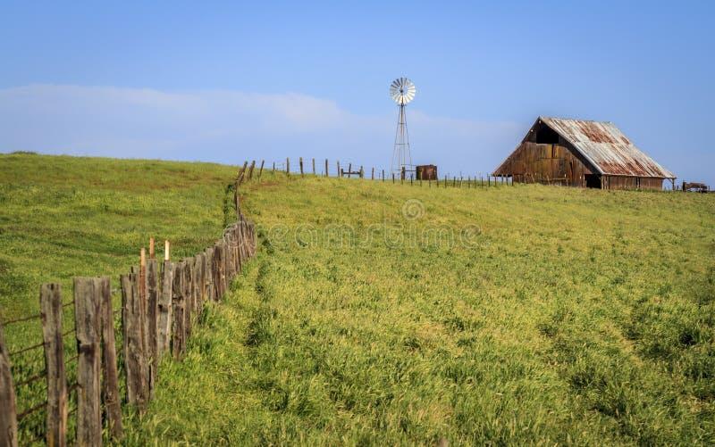 Moinho de vento e celeiro da cerca fotografia de stock
