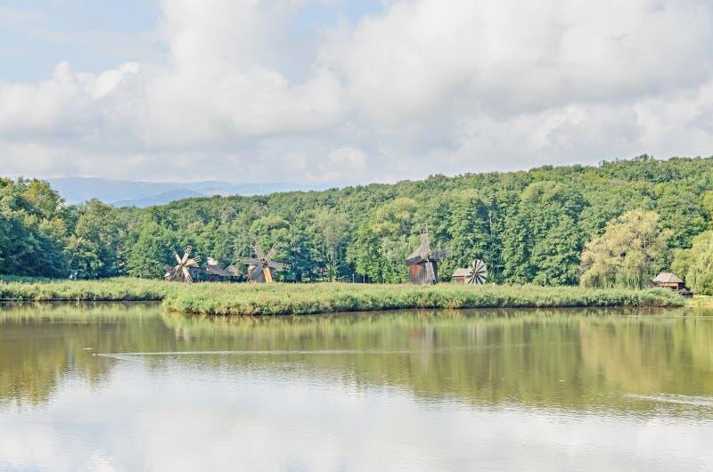 Moinho de vento e watermill perto do lago da água, floresta verde fotografia de stock