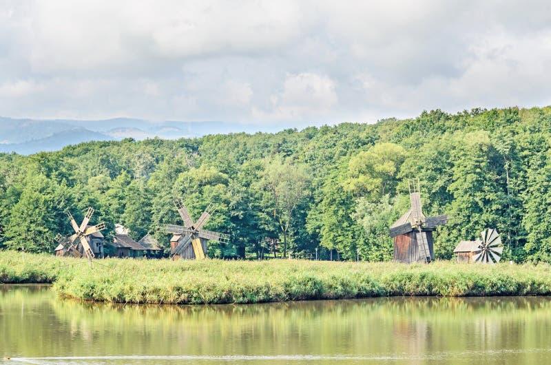 Moinho de vento e watermill perto do lago da água, floresta verde fotos de stock