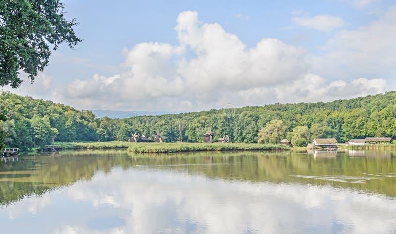 Moinho de vento e watermill perto do lago da água, floresta verde imagem de stock royalty free