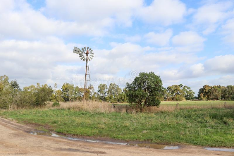 Moinho de vento em uma paisagem australiana rural do céu nebuloso fotografia de stock royalty free