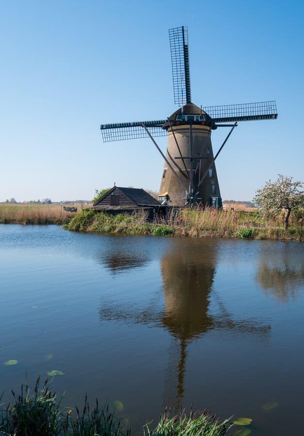Moinho de vento histórico refletido na água em Kinderdijk, Holanda, Países Baixos, um local do patrimônio mundial do UNESCO foto de stock