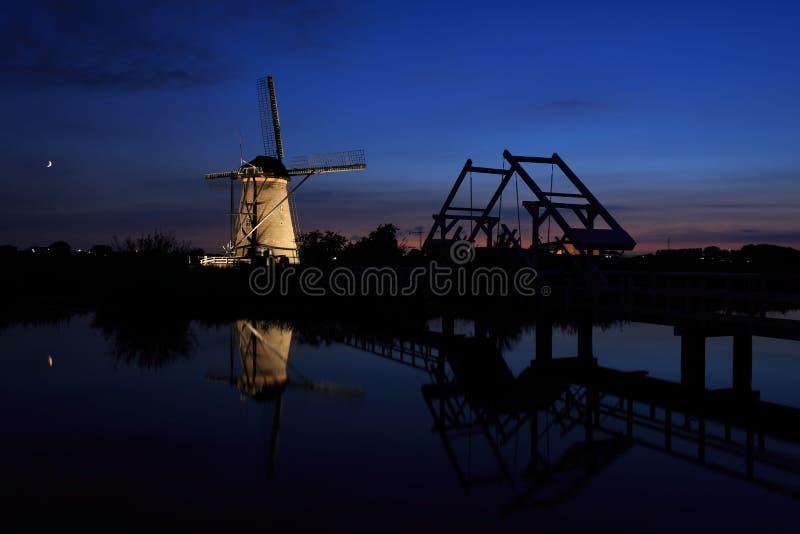 Moinho de vento iluminado e uma ponte levadiça no por do sol imagem de stock