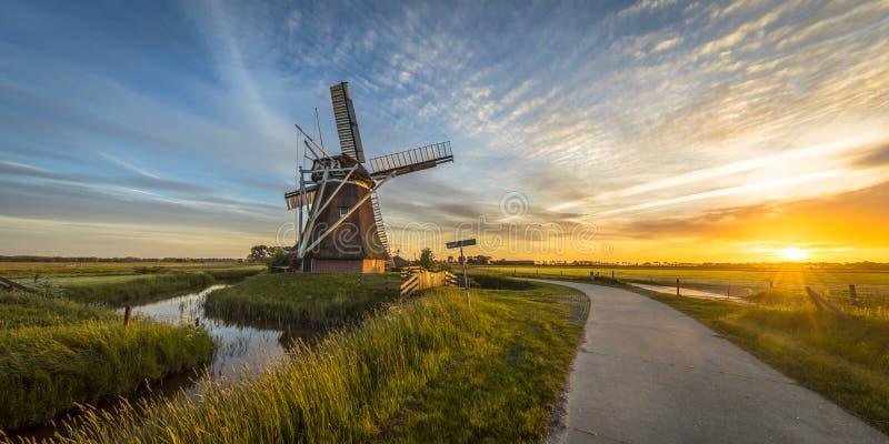 Moinho de vento de madeira com a trilha de ciclismo no por do sol foto de stock royalty free