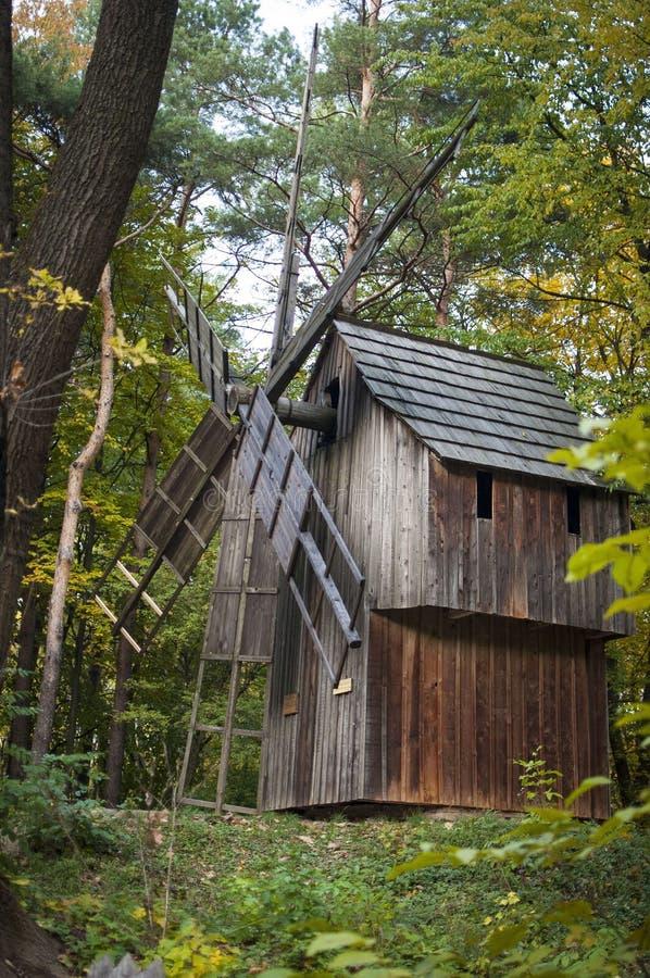 Moinho de vento de madeira no dia do outono entre árvores imagem de stock