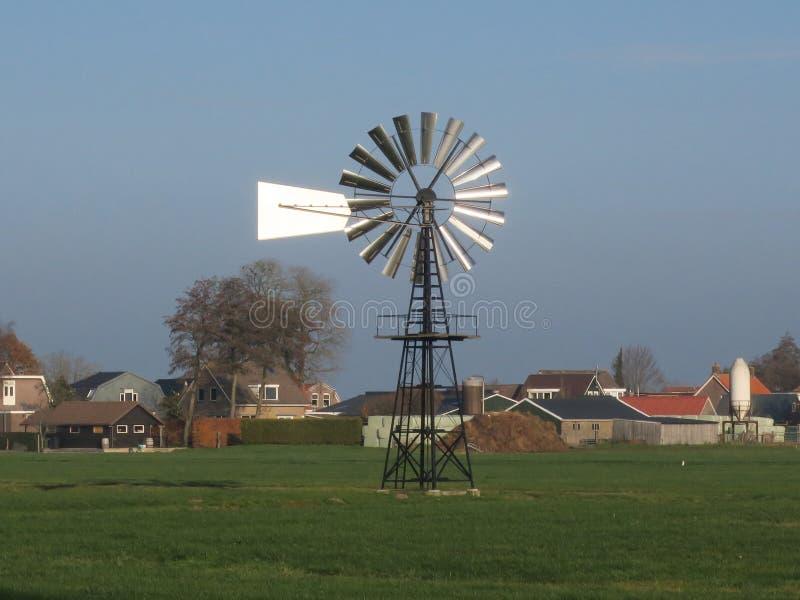 Moinho de vento no prado perto de uma vila em Friesland no inferior fotos de stock royalty free