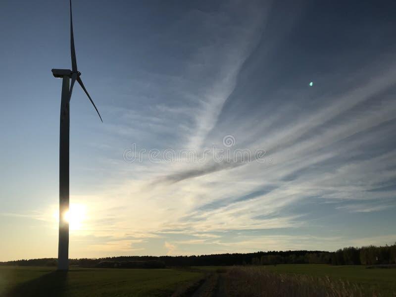 Moinho de vento ou turbina eólica, com o sol de fixação atrás e o espaço livre imagem de stock royalty free