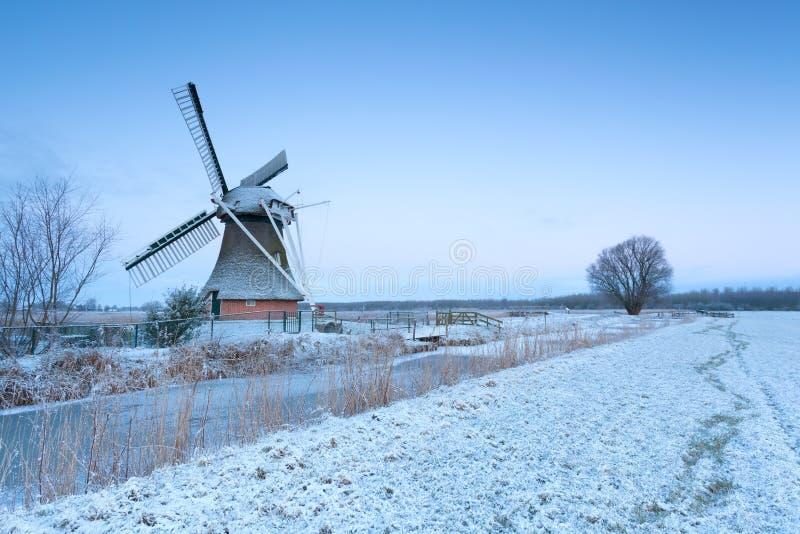 Moinho de vento pelo rio e pelo prado do inverno na neve imagens de stock royalty free