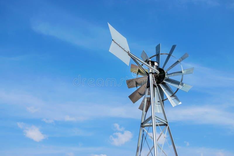Moinho de vento próximo acima da e de fundo do céu azul Turbi do vento do metal imagem de stock royalty free