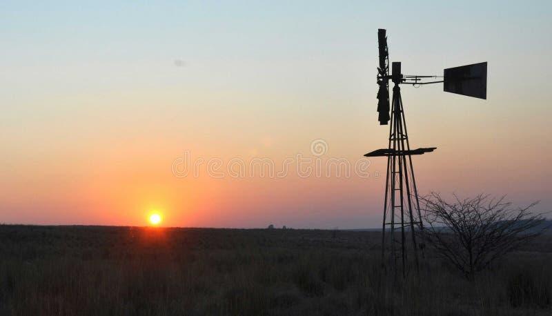 Moinho de vento que olha o nascer do sol imagens de stock royalty free