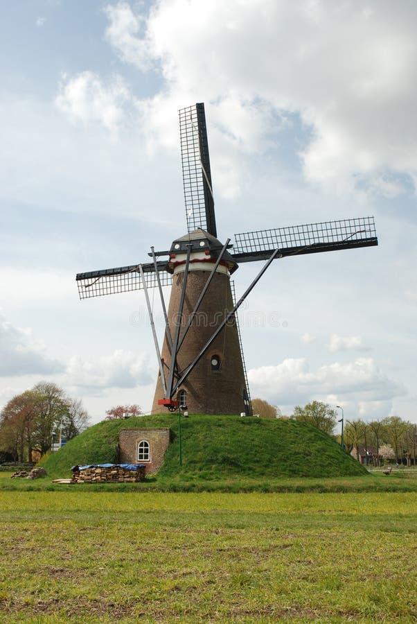 Moinho de vento (traseiro) na paisagem holandesa com nuvens foto de stock