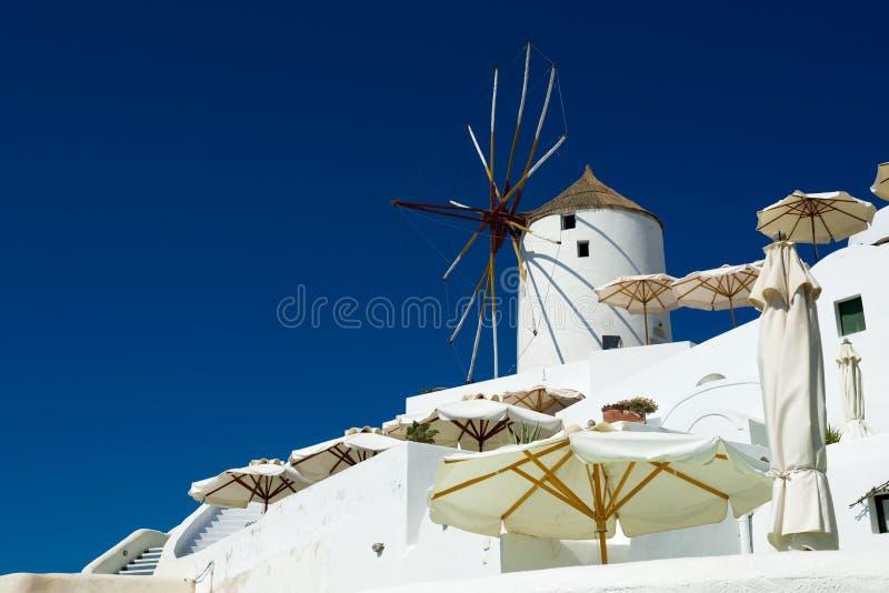 Moinho de vento velho em Oia em um dia ensolarado, Santorini, Grécia fotos de stock