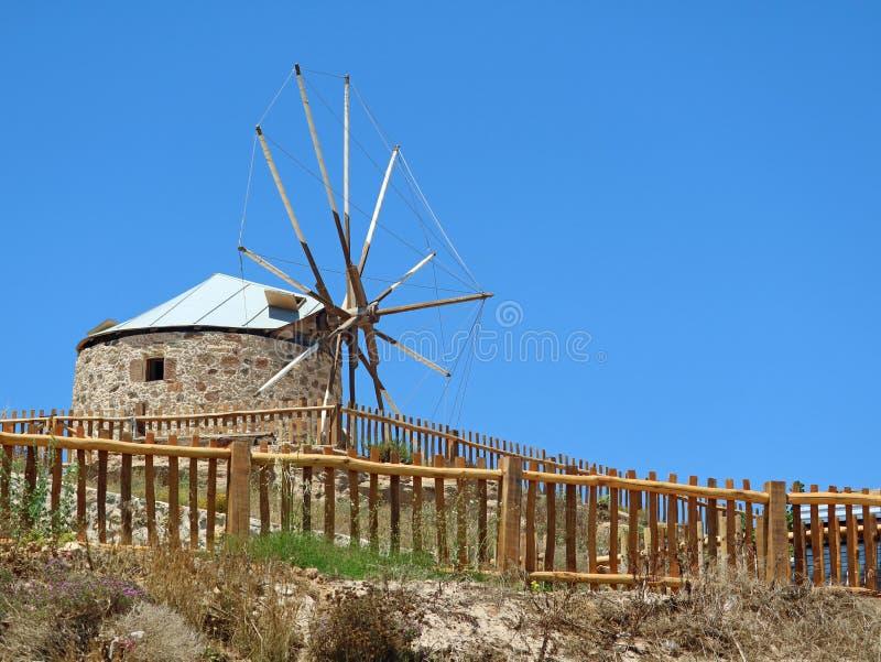 Moinho de vento velho tradicional atrás da cerca de madeira em greece fotografia de stock royalty free