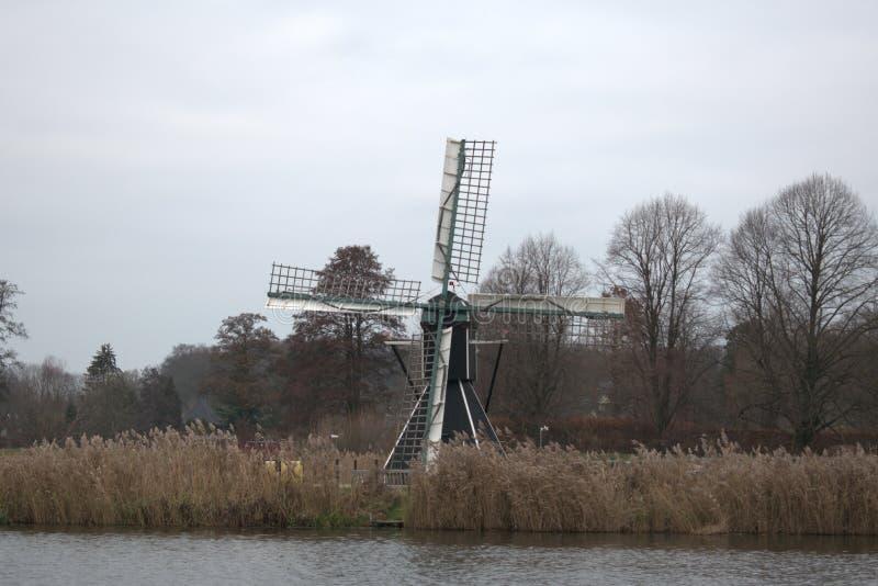 Moinho holandês através de um rio imagens de stock