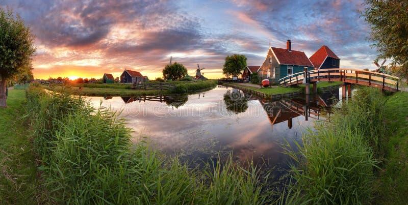 Moinhos de vento da paisagem do panorama no canal da água na vila colorido imagem de stock royalty free