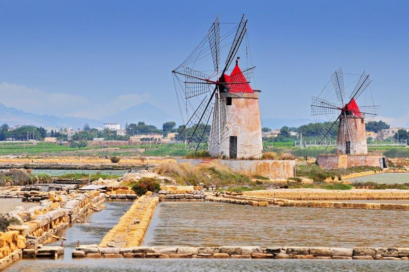 Moinhos de vento e as lagoas do sal da Europa a mais velha em Sicília Itália foto de stock