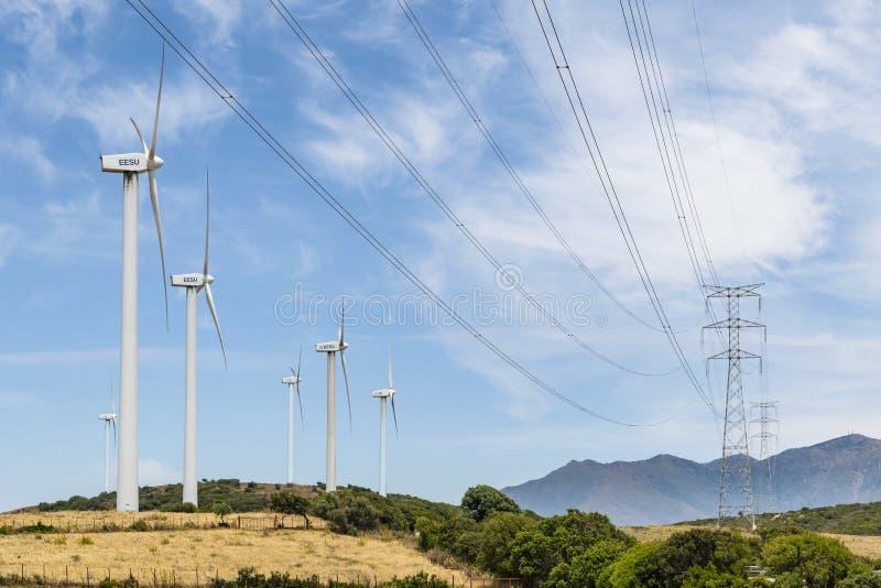 Moinhos de vento e Espanha de Málaga do windfarm do Los Llanos das linhas de alta tensão foto de stock