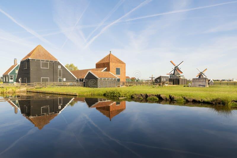 Moinhos de vento holandeses tradicionais com o canal em Zaanse Schans em Amste imagens de stock royalty free