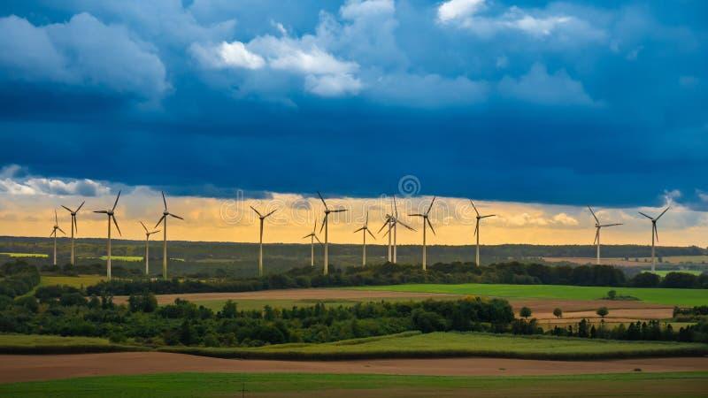 Moinhos de vento nas planícies bonitas e verdes fotografia de stock