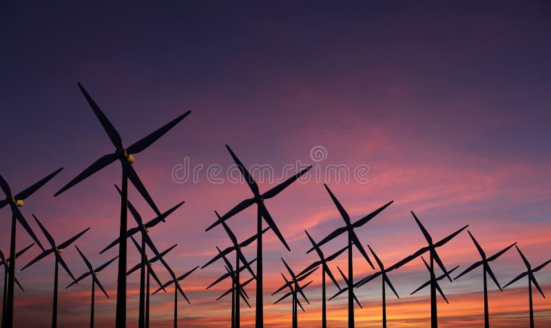 Moinhos de vento no por do sol da noite - sustainablilty imagem de stock royalty free
