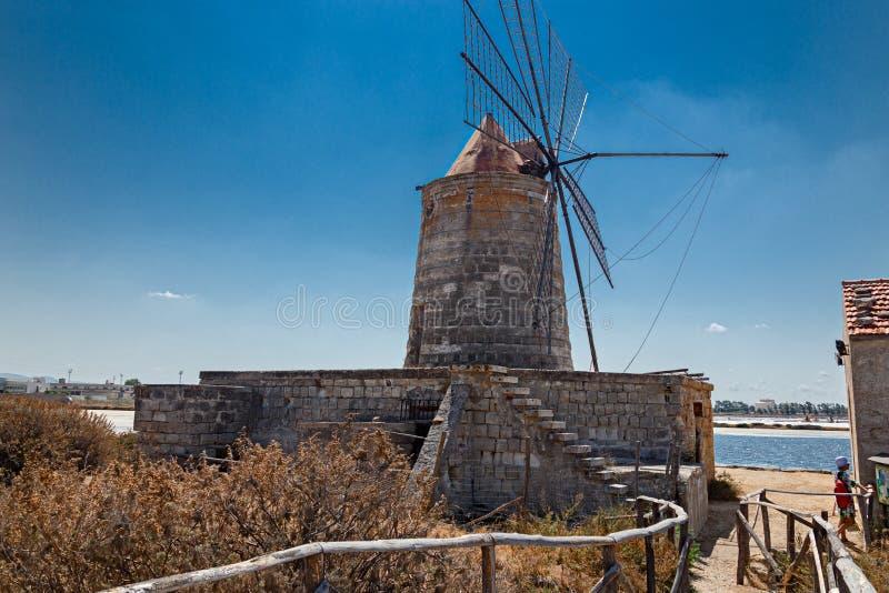 Moinhos de vento velhos nas bandejas de sal de Trapani em Sicília fotos de stock