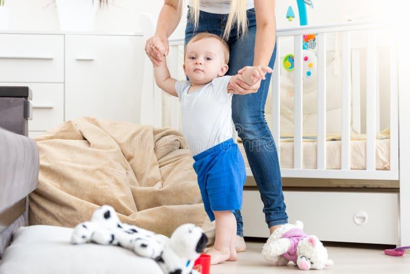 10 mois de garçon d'enfant en bas âge apprenant faisant des premières étapes avec la mère images libres de droits
