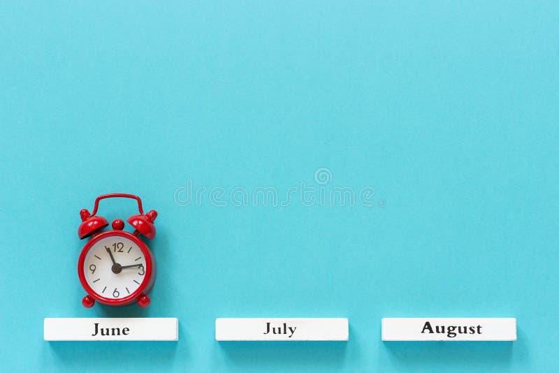 Mois en bois d'été de calendrier et réveil rouge au-dessus de juin sur le fond bleu Configuration plate créative de vue supérieur image libre de droits