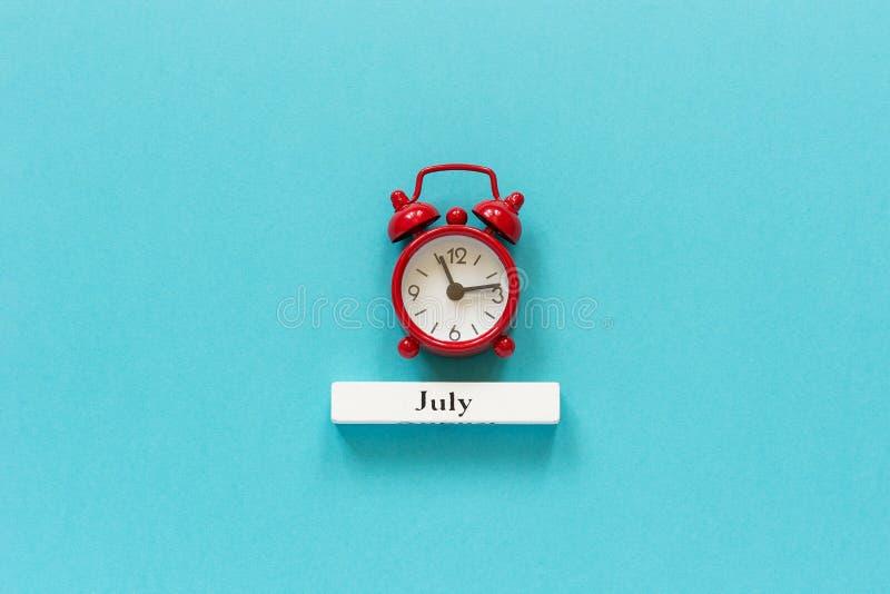 Mois en bois juillet d'été de calendrier et réveil rouge sur le fond de papier bleu Concept bonjour juillet ou au revoir dessus c photographie stock libre de droits