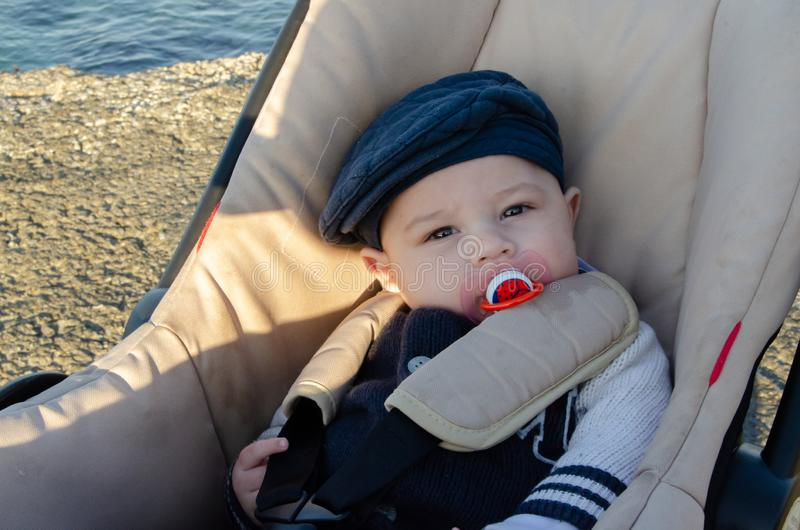 4 mois mignons de bébé garçon s'asseyant dans la poussette sur la plage avec le chapeau bleu et la tétine rouge images libres de droits