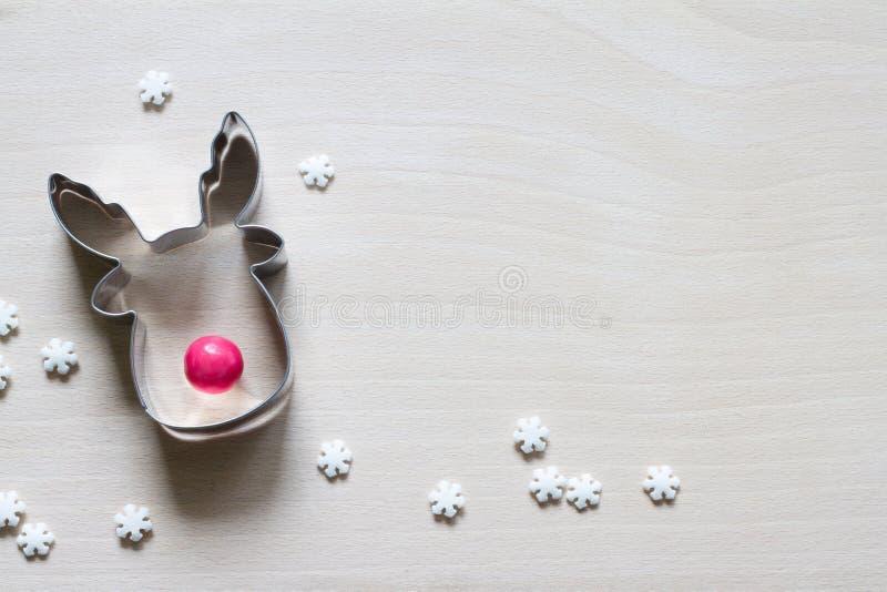 Moisissure de biscuits de rennes avec nez rouge de bonbons et flocons de neige de sucre sur la planche à découper Contexte du con image libre de droits