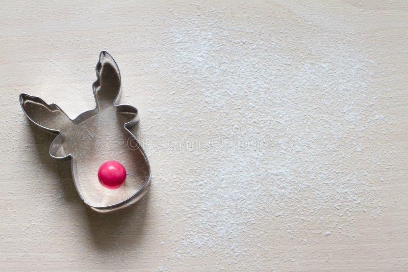 Moisissure de biscuits de rennes avec nez rouge et farine de bonbons sur la planche à découper Contexte du concept de Noël image stock
