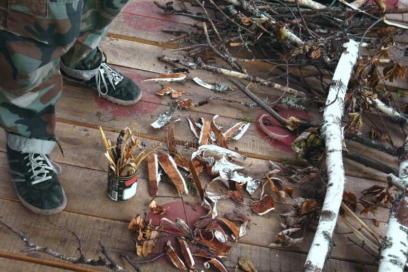 Moisson des puces et de l'écorce pour un feu par temps pluvieux Production d'une torche au moyen d'une boîte en fer blanc Bois de images stock