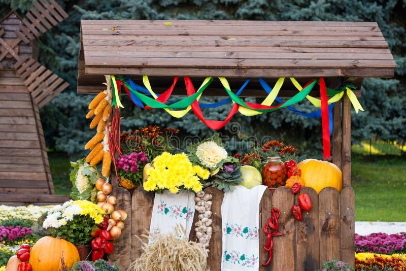 Moissonnez les légumes sur le commerce équitable dans un pavillon en bois Exposition ukrainienne traditionnelle saisonnière des a illustration libre de droits