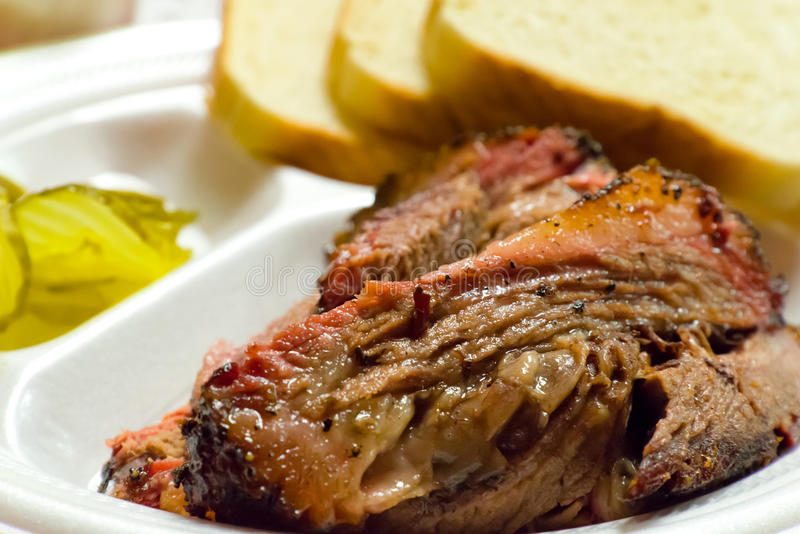 Moist barbecue brisket. Close up of a fatty barbecue brisket picnic plate, including white bread and pickles stock image