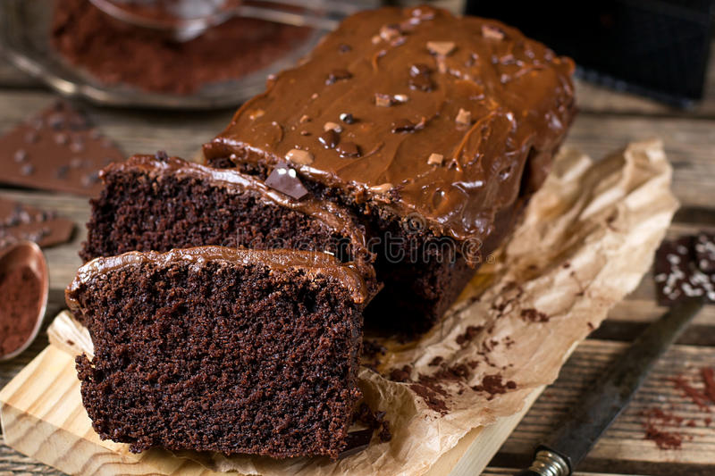 Moist chocolate cake with milk chocolate topping glaze. And cocoa powder stock photography
