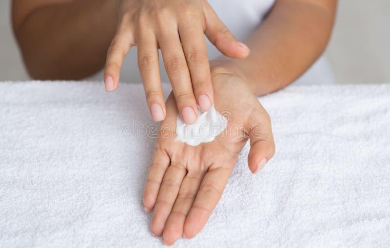 Moisturize Skin. Woman Spreading Nourishing Cream on Palm. Against Towel royalty free stock image