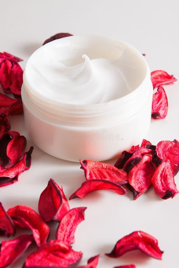Moisturizing сливк и лепестки розы на белизне стоковые фотографии rf