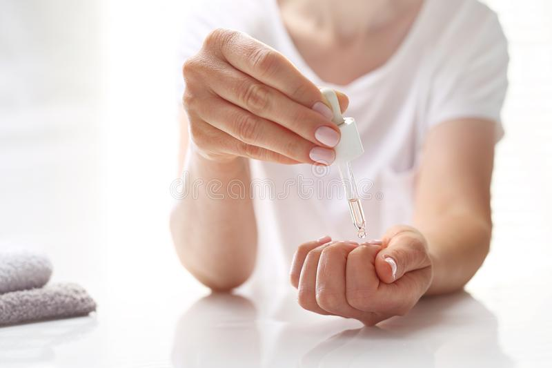 Moisturizing oil for cuticles. The woman cares for hands and nails stock photo