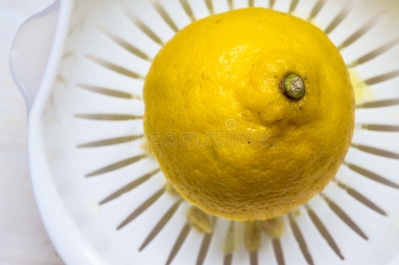 Moitié d'un citron dans un presse-fruits photographie stock libre de droits