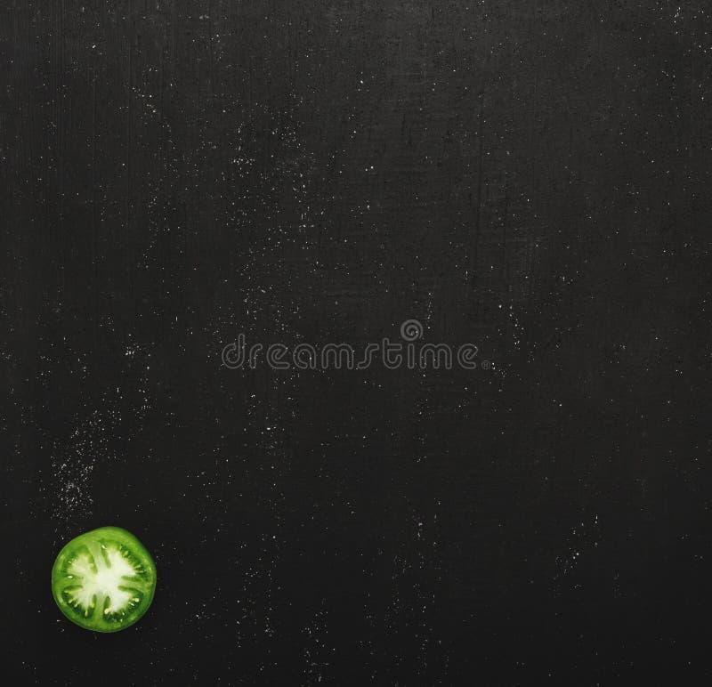 Moitié d'une tomate verte juteuse sur un fond en pierre noir Concept des légumes frais, de la vue supérieure et de l'espace de co photographie stock libre de droits