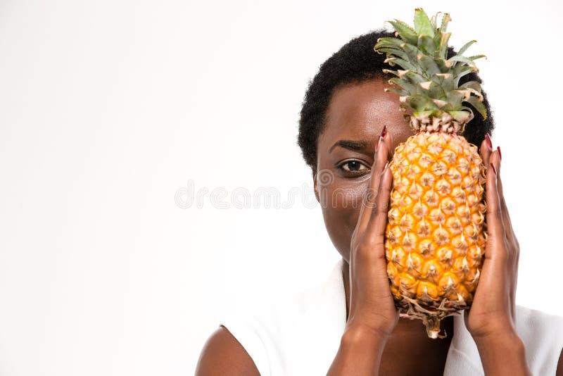 Moitié de dissimulation de belle femme d'afro-américain de visage avec l'ananas photos libres de droits
