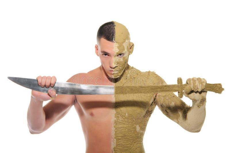 Moitié de jeune homme enduite de l'argile avec l'épée \ photographie stock libre de droits