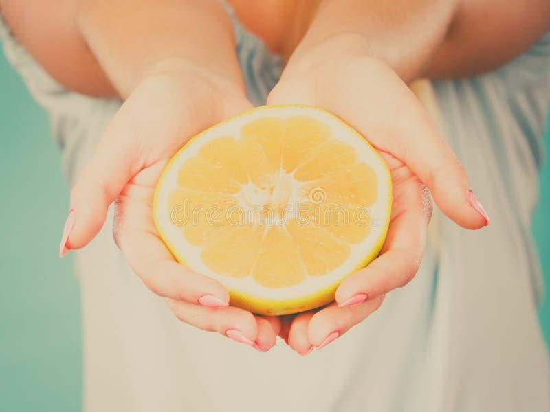 Moitié des agrumes jaunes de pamplemousse dans la main humaine photos stock