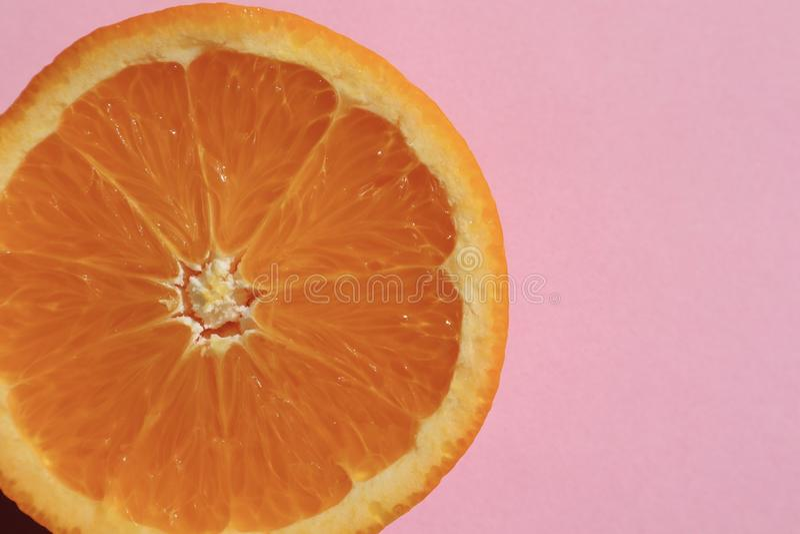 Moitié orange sur Pale Pink Background images stock