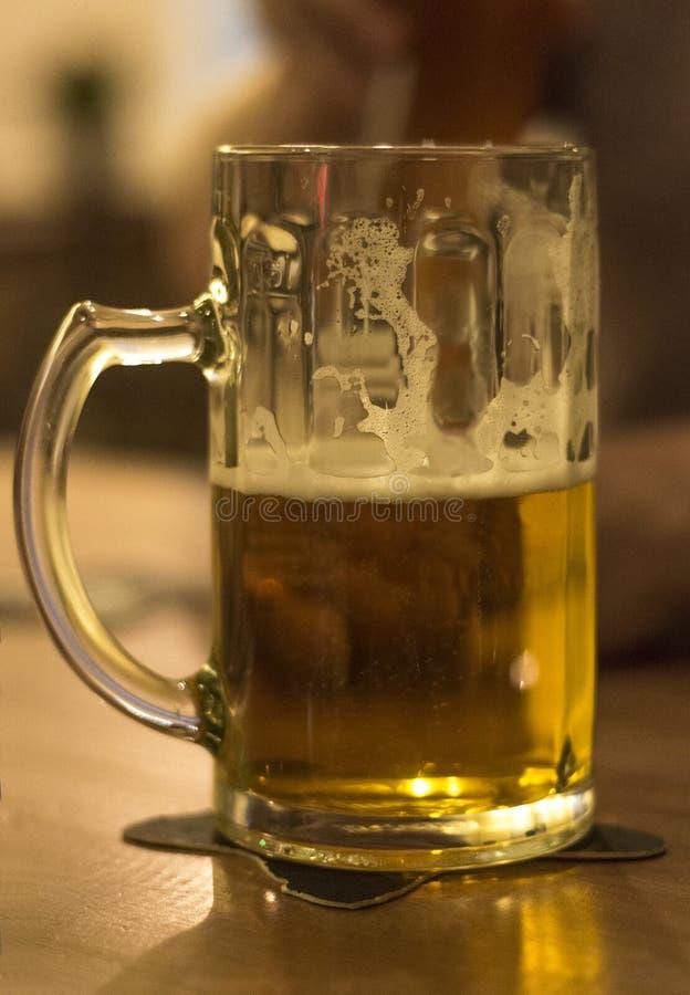 Moitié par en verre de bière image stock