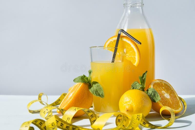 Moitiés d'orange fraîche, citron, verre de jus d'orange, bouteille de jus d'orange, bande de mesure, agrume, jus de fruit images libres de droits