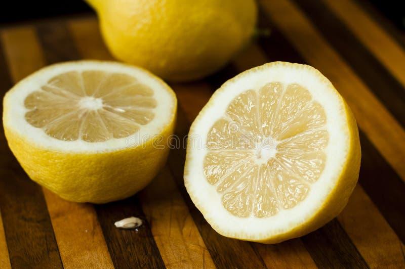 Moitiés de citron sur la planche à découper photos stock