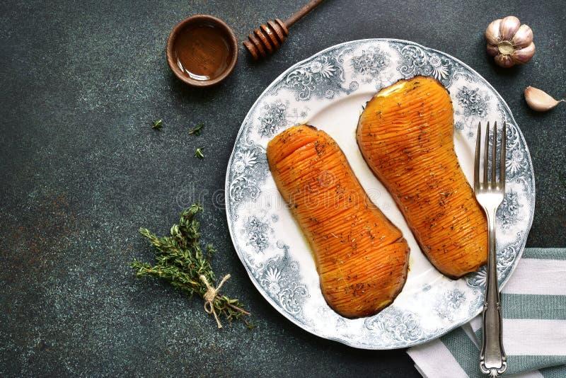 Moitiés de courge de butternut cuites au four avec du miel et des herbes sur un vinta photographie stock