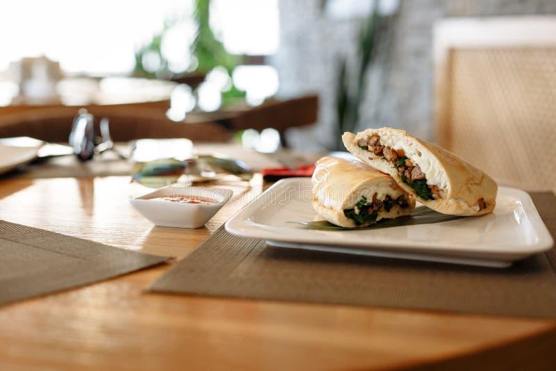 Moitiés de pizza de Calzone sur la feuille en bambou dans le plat carré sur la table en bois images stock