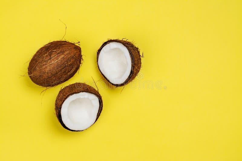 Moitiés et feuilles de noix de coco sur le fond jaune images stock